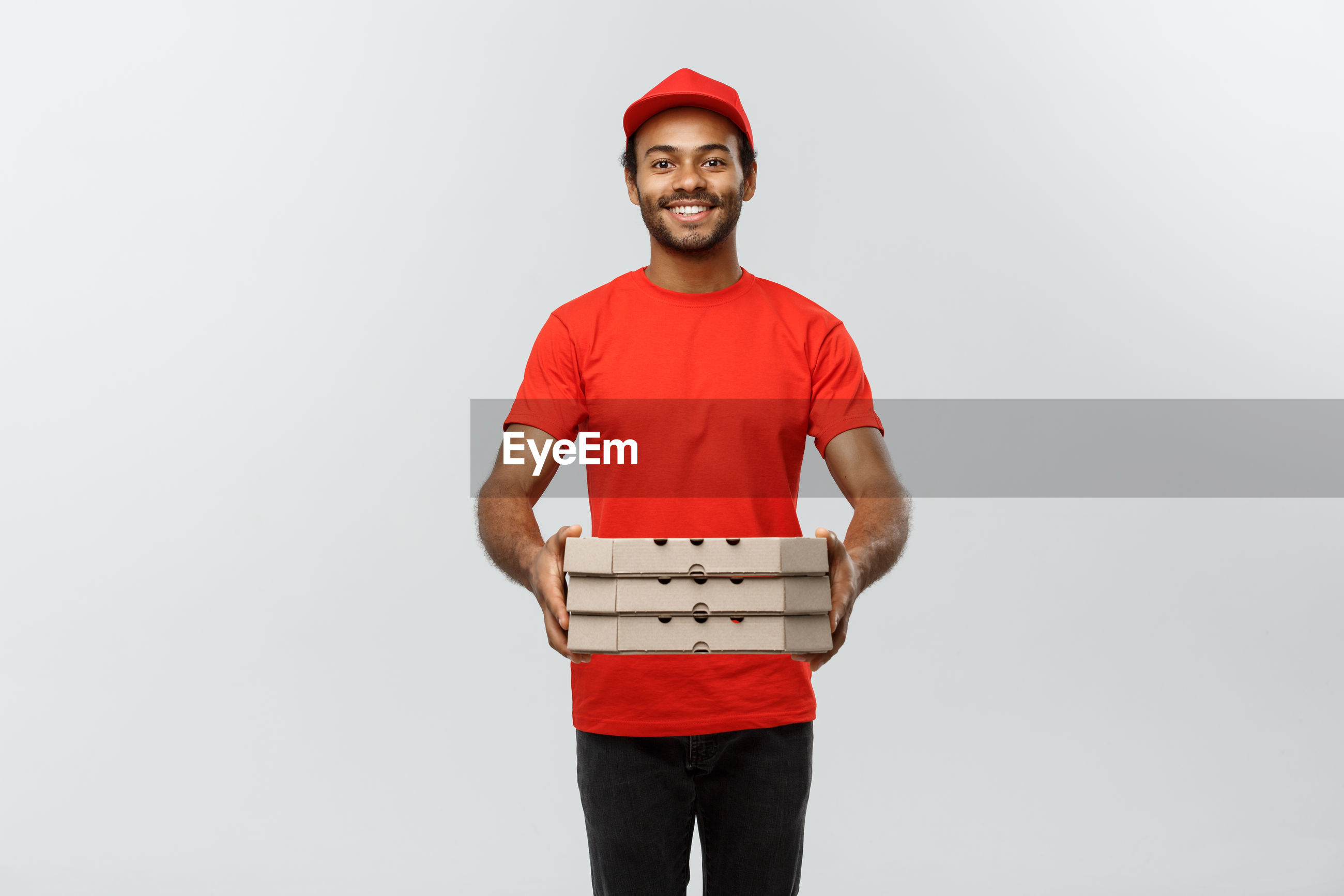 Portrait of young delivery man holding cardboard box against white background
