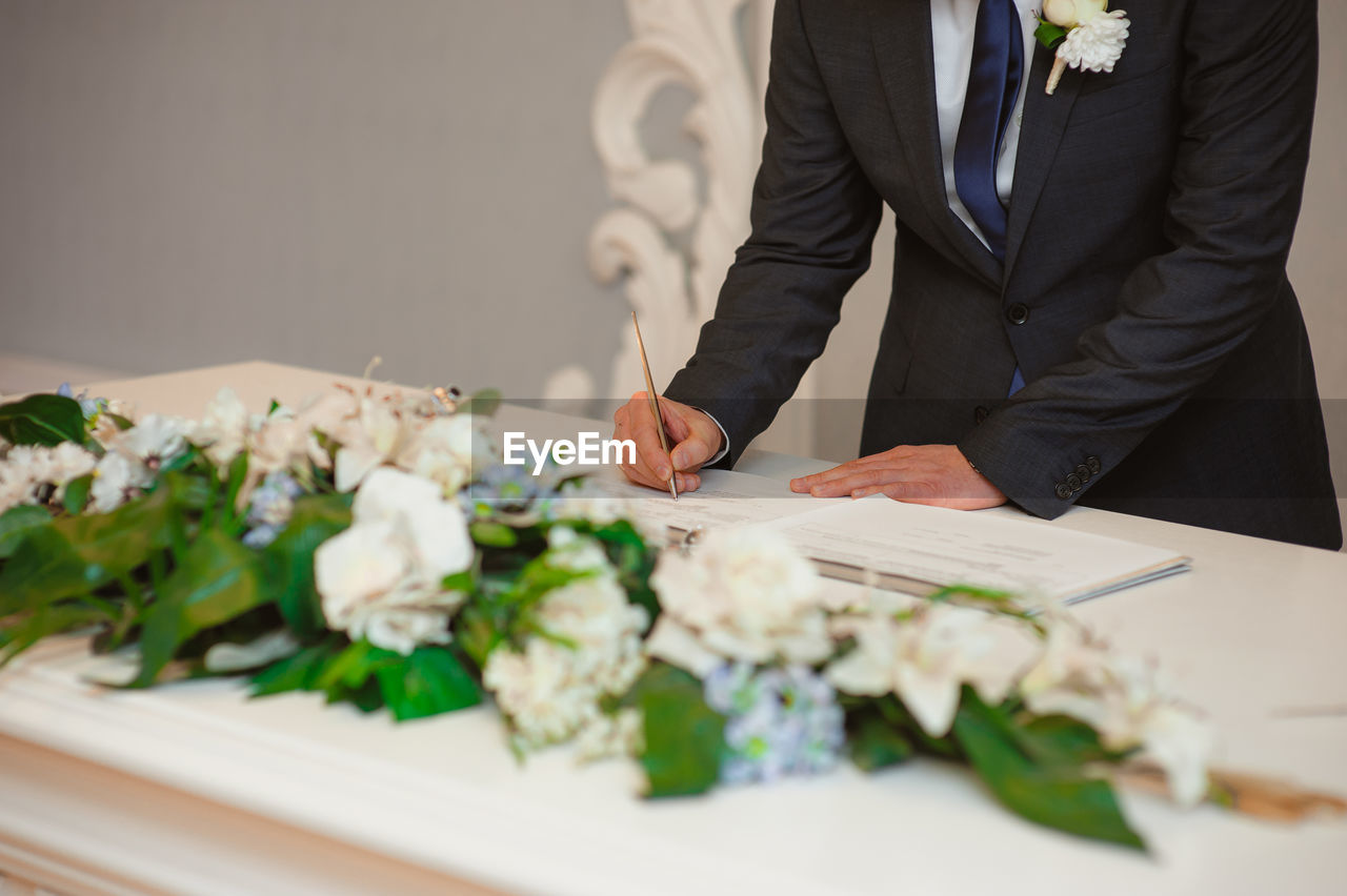 MIDSECTION OF MAN AND WOMAN STANDING BY FLOWER BOUQUET