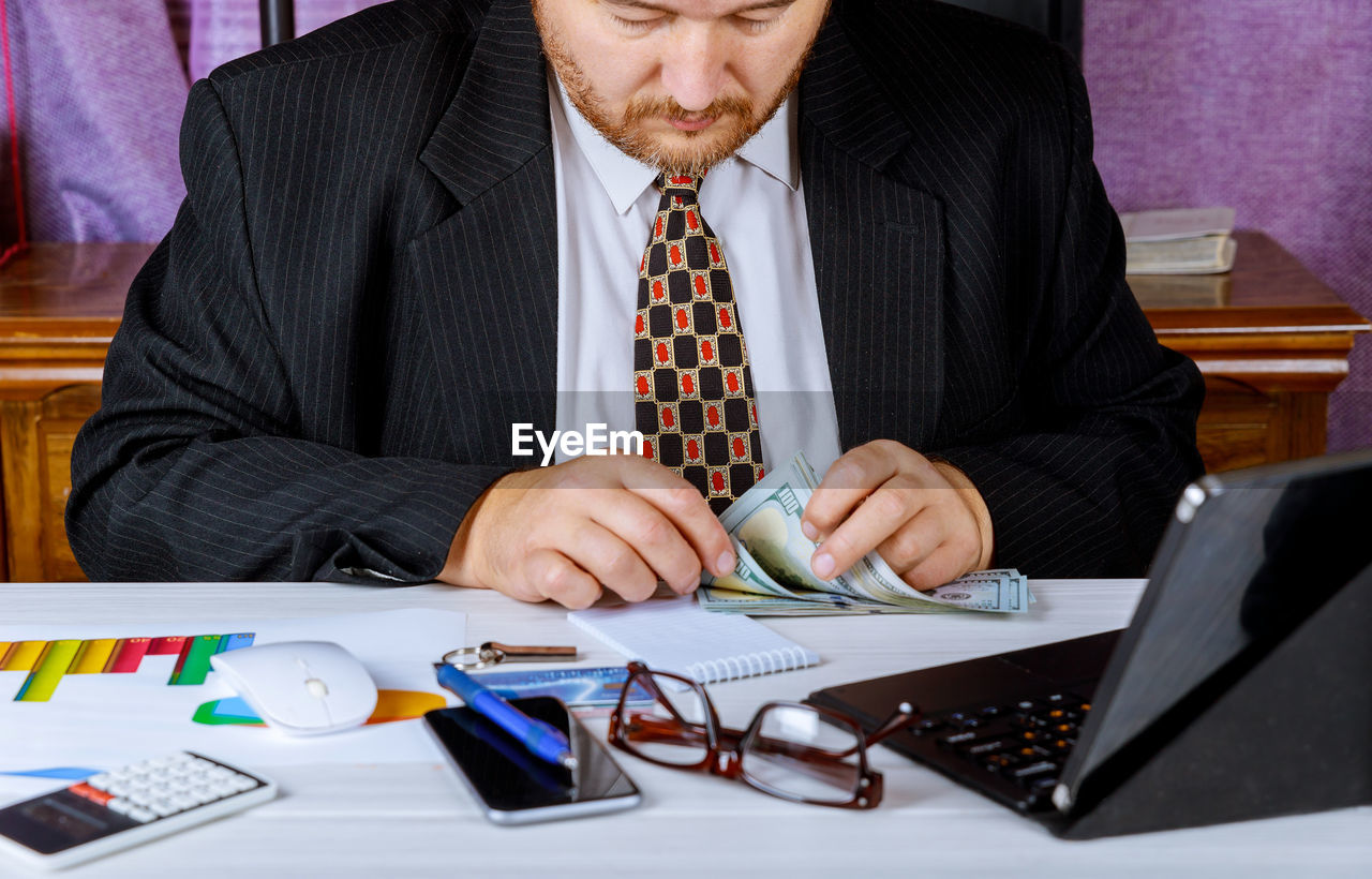 business, businessman, business person, table, office, men, adult, corporate business, males, technology, furniture, desk, suit, computer, well-dressed, indoors, working, occupation, businesswear, sitting, necktie, formal businesswear, menswear, wireless technology, using laptop, financial advisor