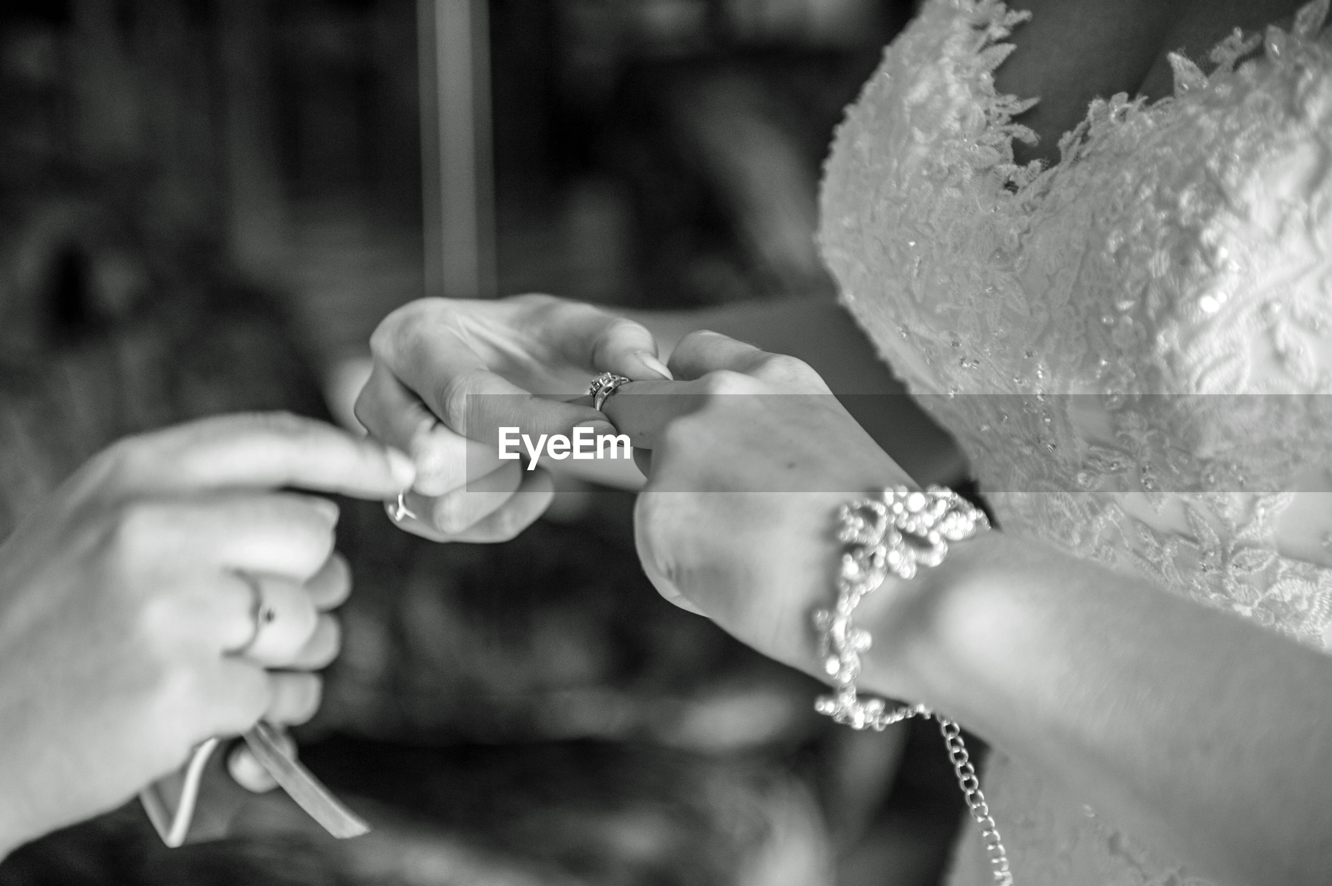 Close-up of bride putting rings in finger with person