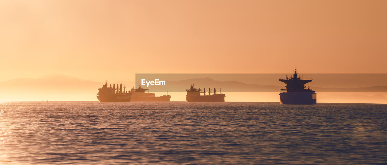 water, sky, sunset, sea, orange color, nautical vessel, transportation, waterfront, no people, mode of transportation, silhouette, nature, beauty in nature, ship, industry, scenics - nature, outdoors, oil industry, copy space, cruise ship