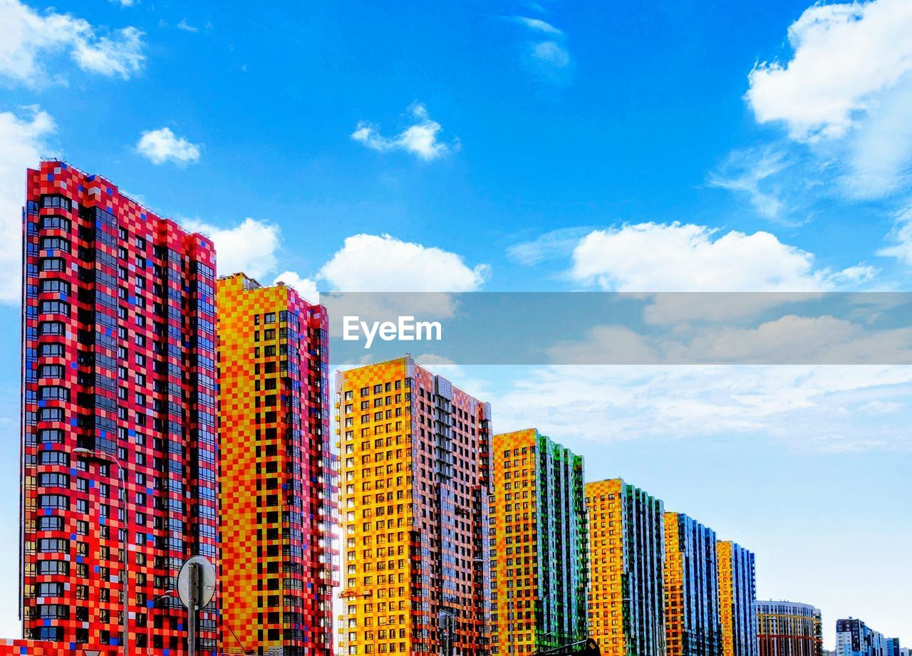 Low angle view of multi colored modern buildings against sky