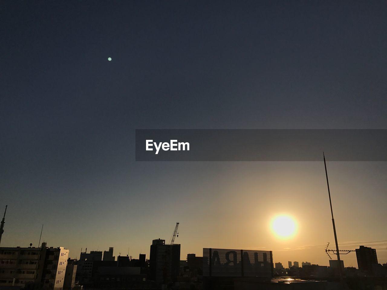 sunset, architecture, building exterior, city, built structure, sun, silhouette, sky, cityscape, moon, no people, skyscraper, outdoors