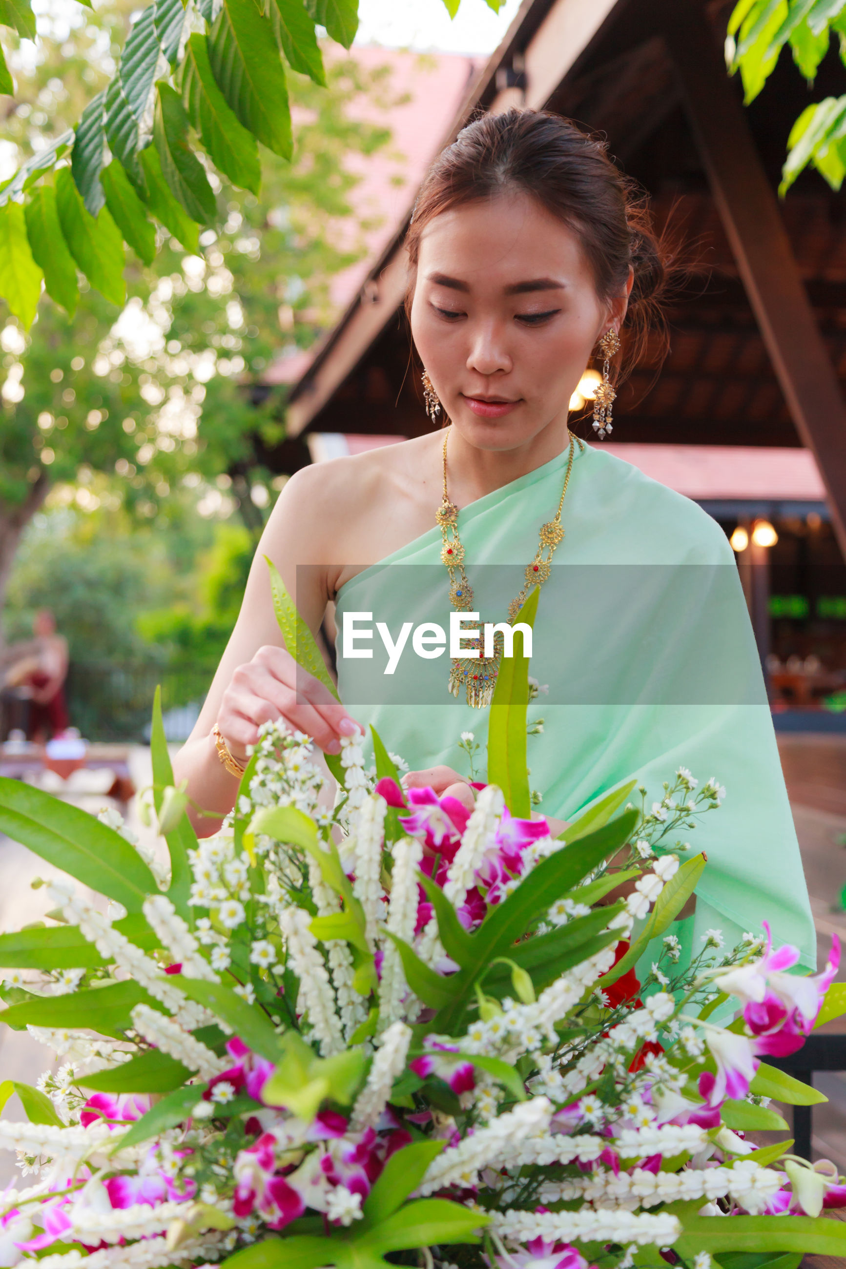 Young woman wearing traditional clothing while arranging flowers outdoors