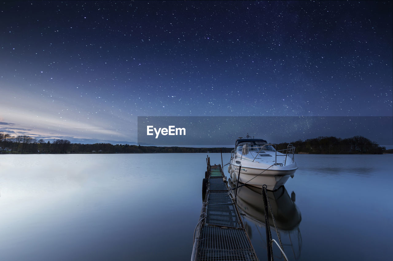 Boat Moored By Jetty In Lake Against Sky At Night