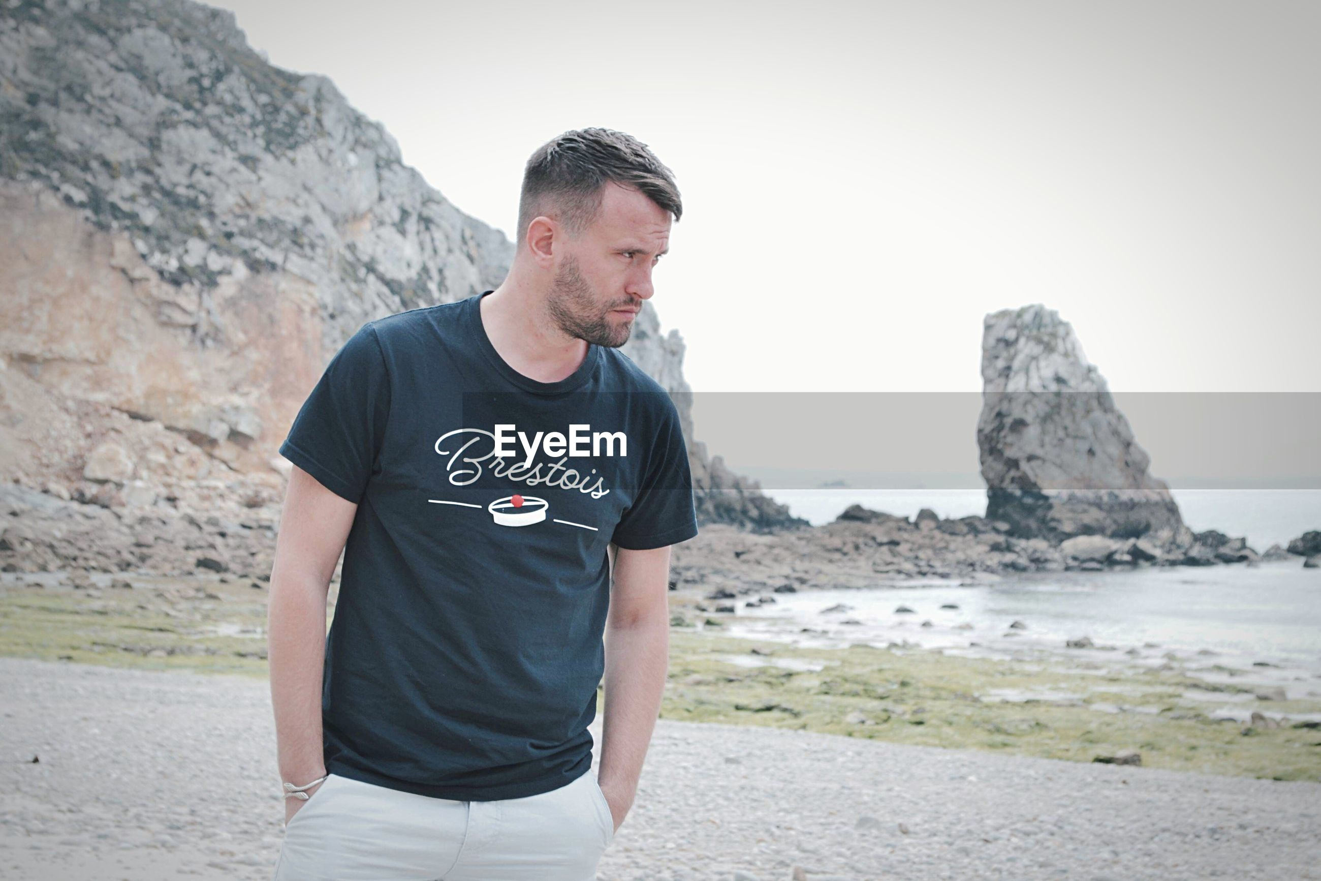 MAN LOOKING AWAY WHILE STANDING ON ROCK