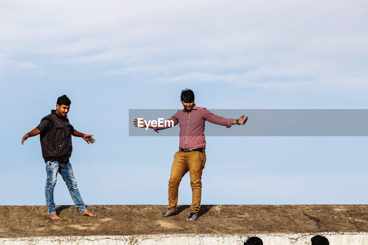 Men With Arms Outstretched Standing On Retaining Wall Against Sky