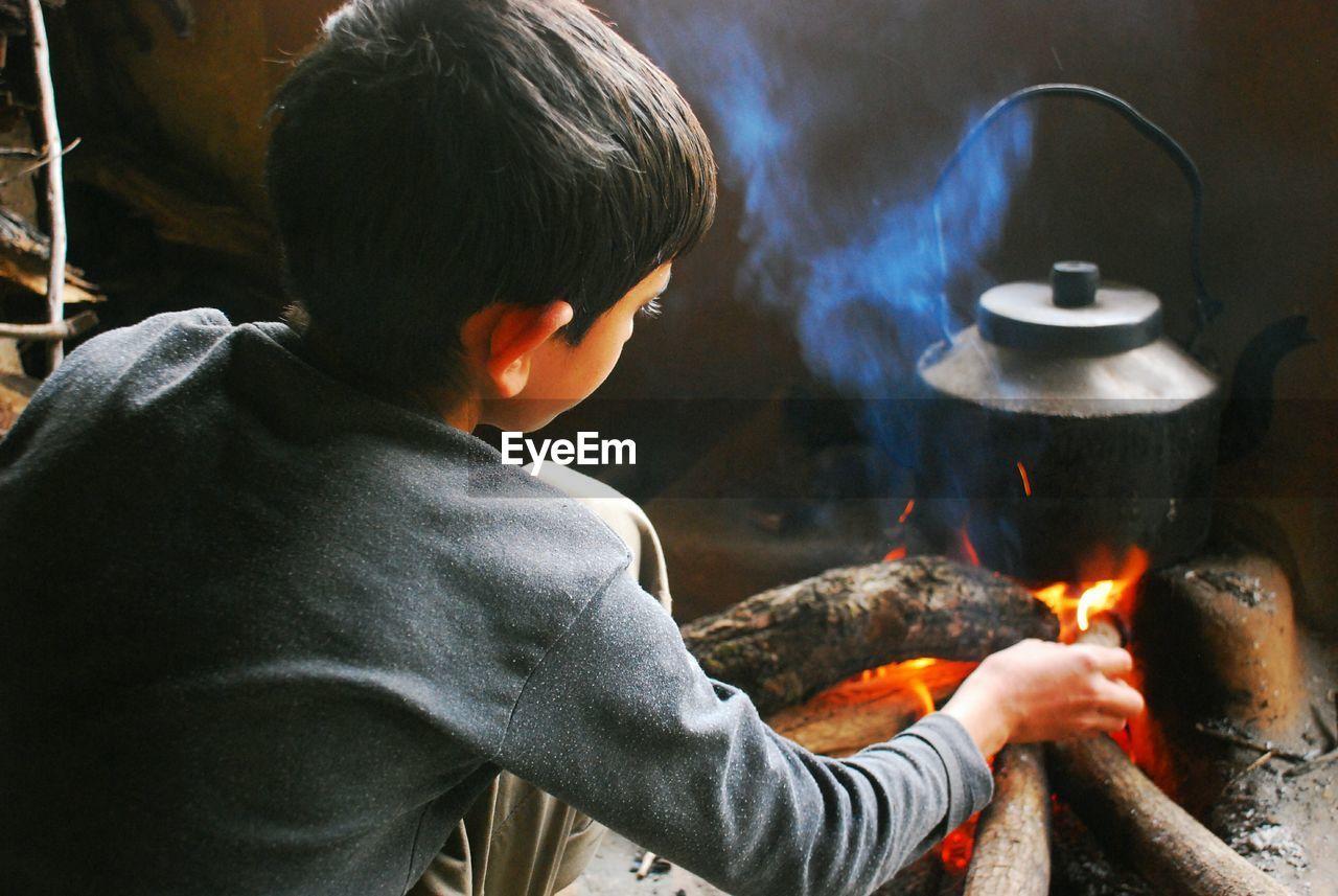Boy Preparing Chai In Kettle On Fire