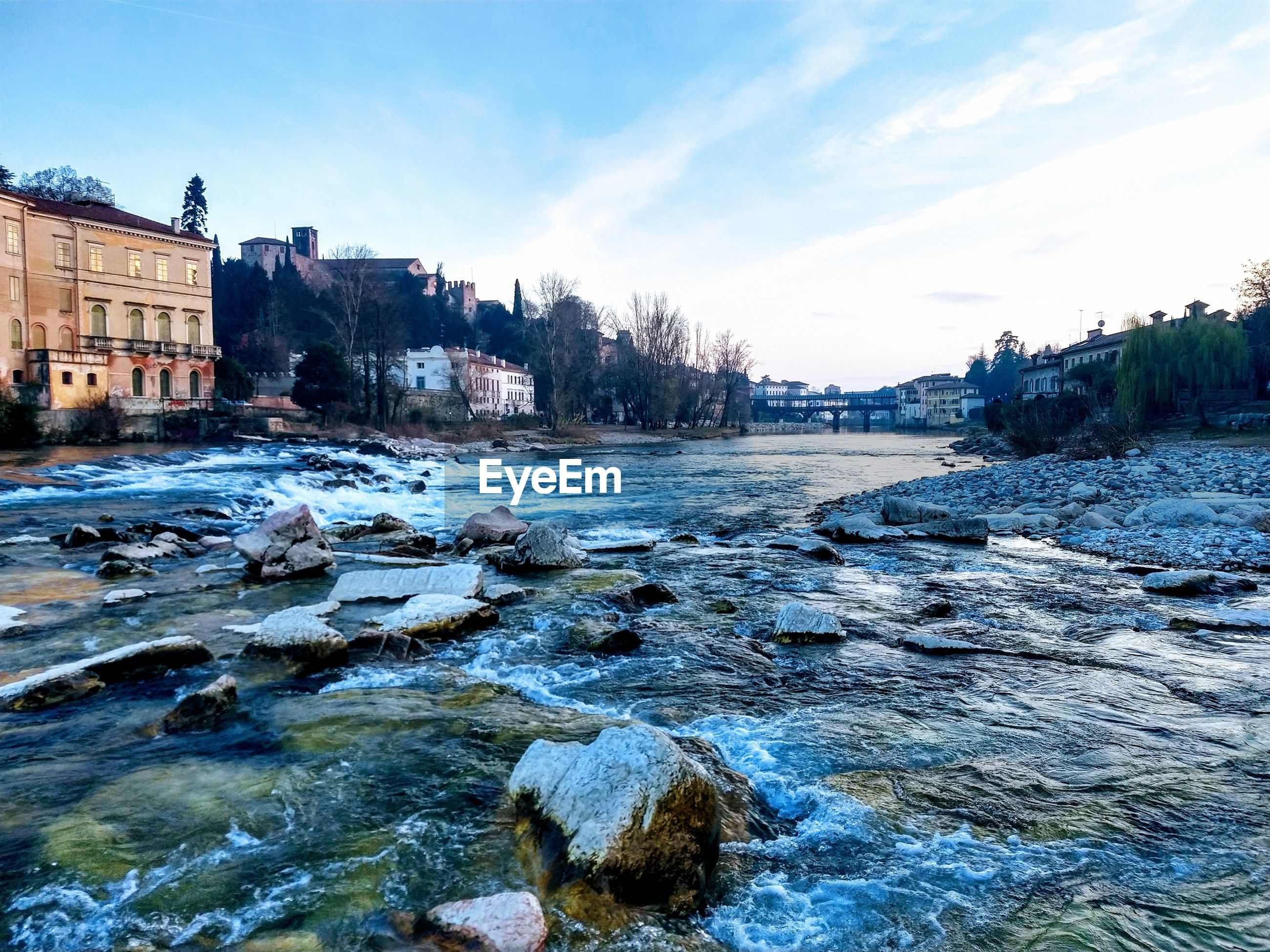 RIVER FLOWING BY ROCKS AGAINST SKY