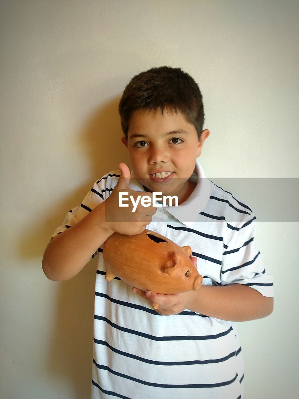 Portrait Of Boy With Piggy Bank Showing Thumbs Up At Home