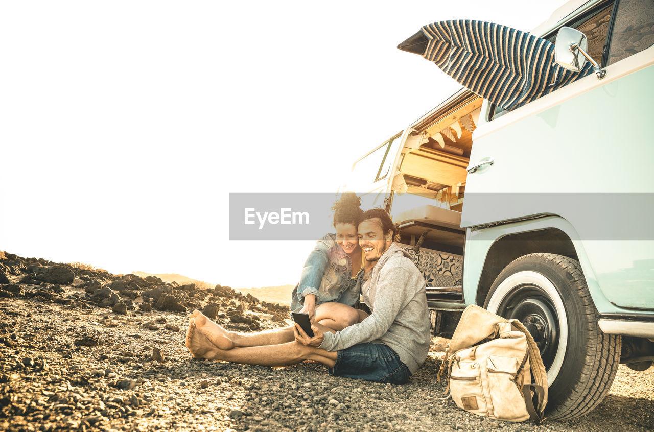 Couple sitting by van against sky
