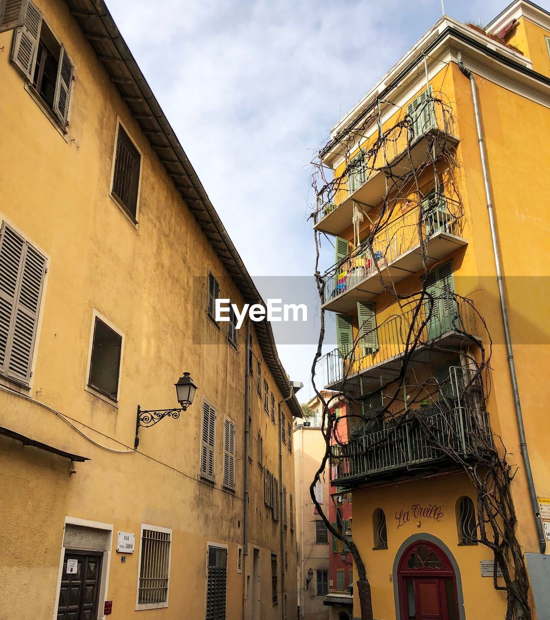 building exterior, architecture, built structure, low angle view, building, window, residential district, sky, no people, day, cloud - sky, yellow, outdoors, nature, city, fire escape, apartment, balcony, lighting equipment, street