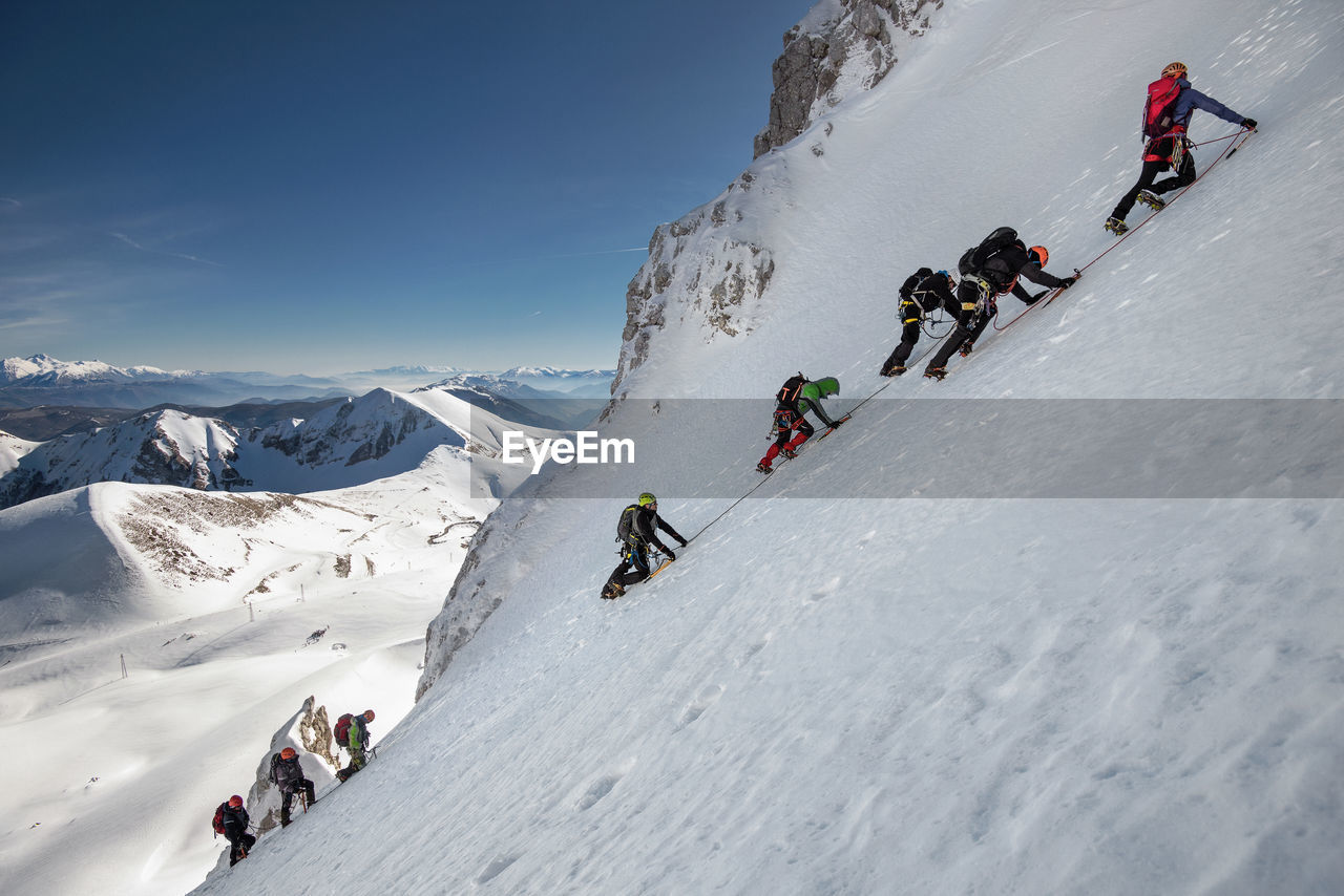 People Climbing On Snowcapped Mountains During Winter