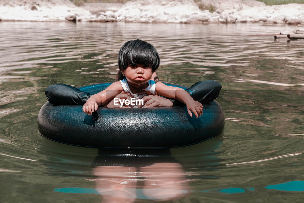 Girl with mother amidst inflatable ring swimming in lake