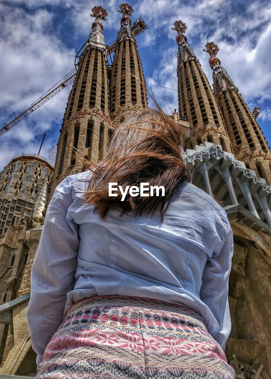 Low Angle View Of Woman Standing Against Barcelona Cathedral