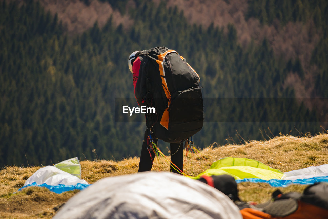 real people, men, rear view, one person, day, lifestyles, land, nature, leisure activity, selective focus, clothing, outdoors, occupation, activity, field, unrecognizable person, mountain, standing, plant