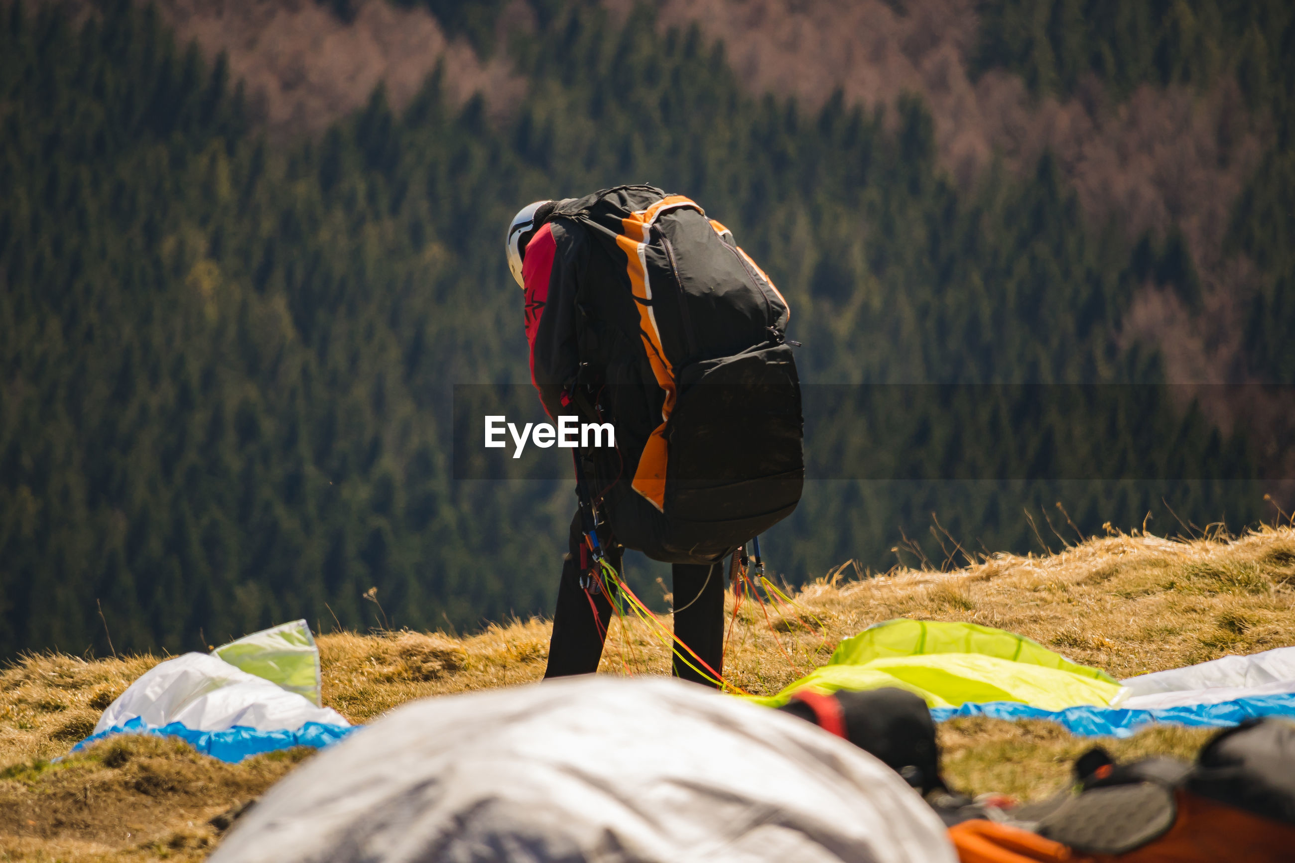 REAR VIEW OF PERSON STANDING ON FIELD AGAINST MOUNTAIN