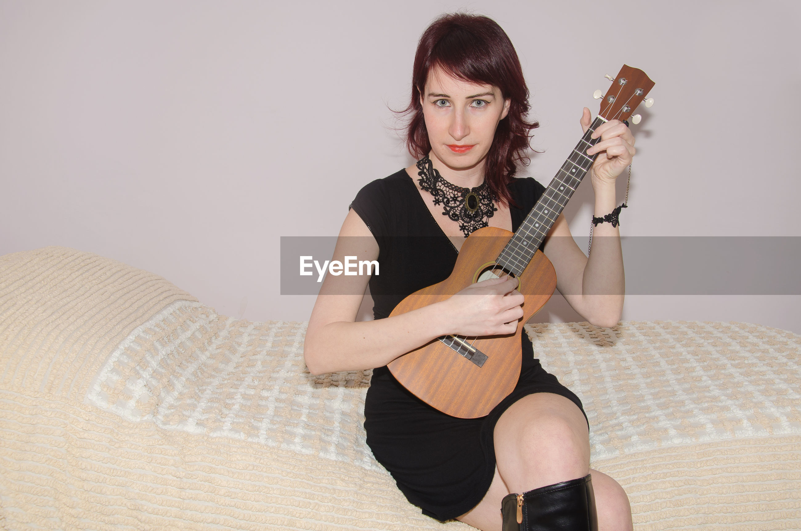 Portrait of woman playing guitar while sitting on bed