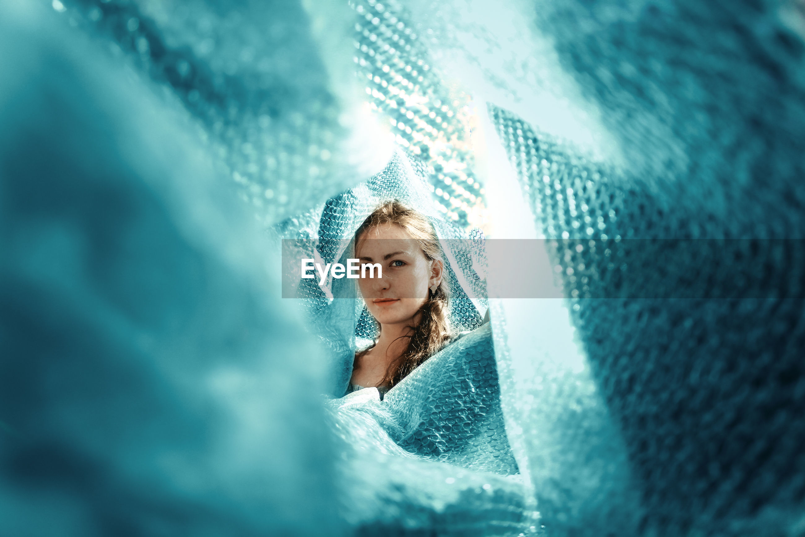 Portrait of beautiful woman surrounded with blue textiles