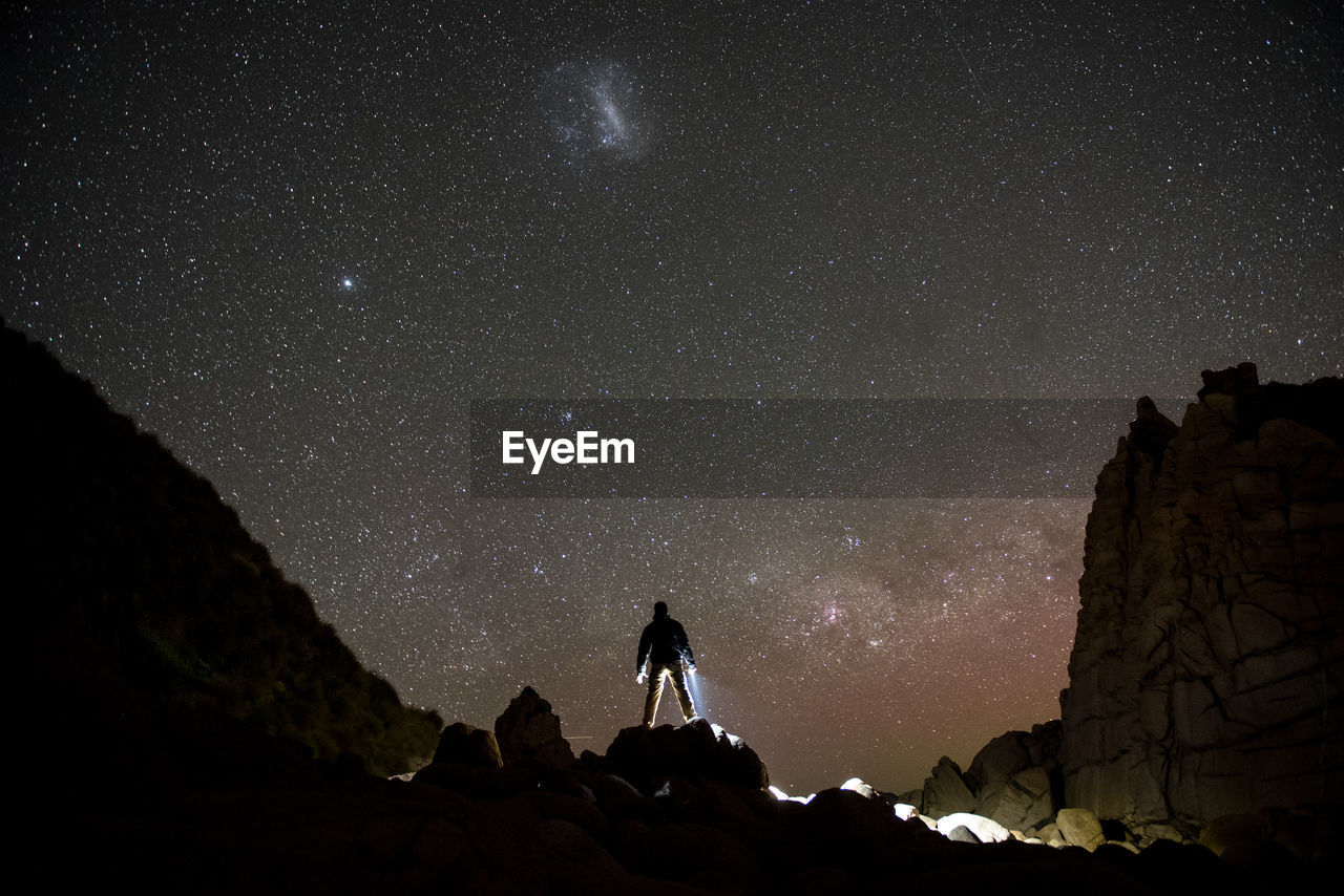 Silhouette man standing on rock against star field at night