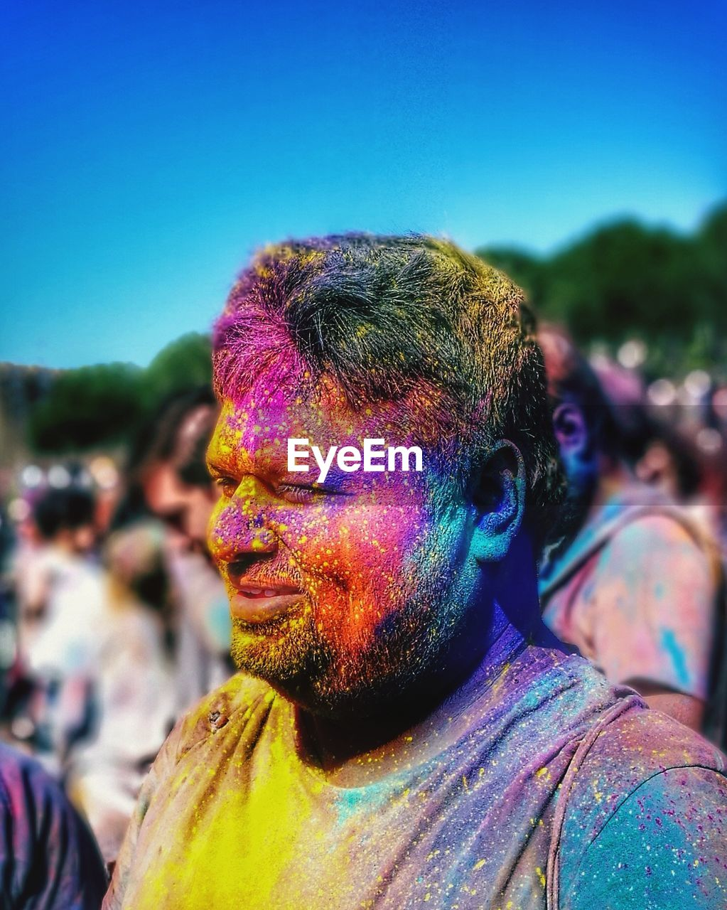 Close-up of man covered with multi colored powder paint against sky
