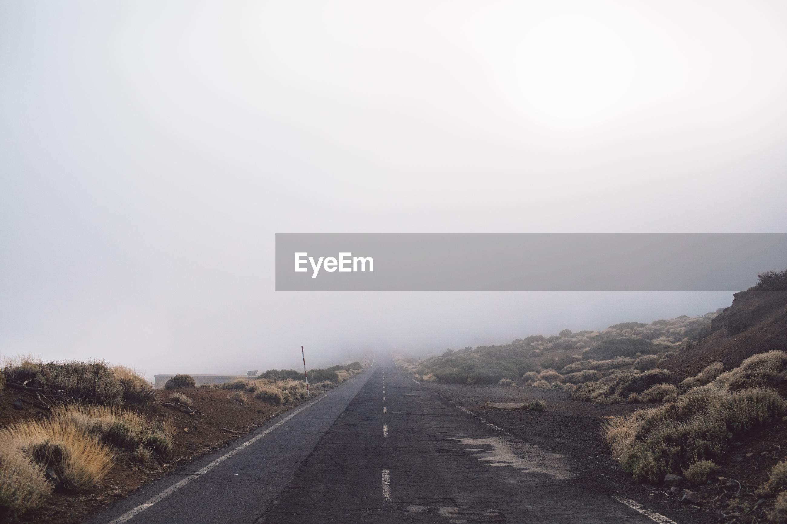 ROAD LEADING TOWARDS SKY DURING FOGGY WEATHER