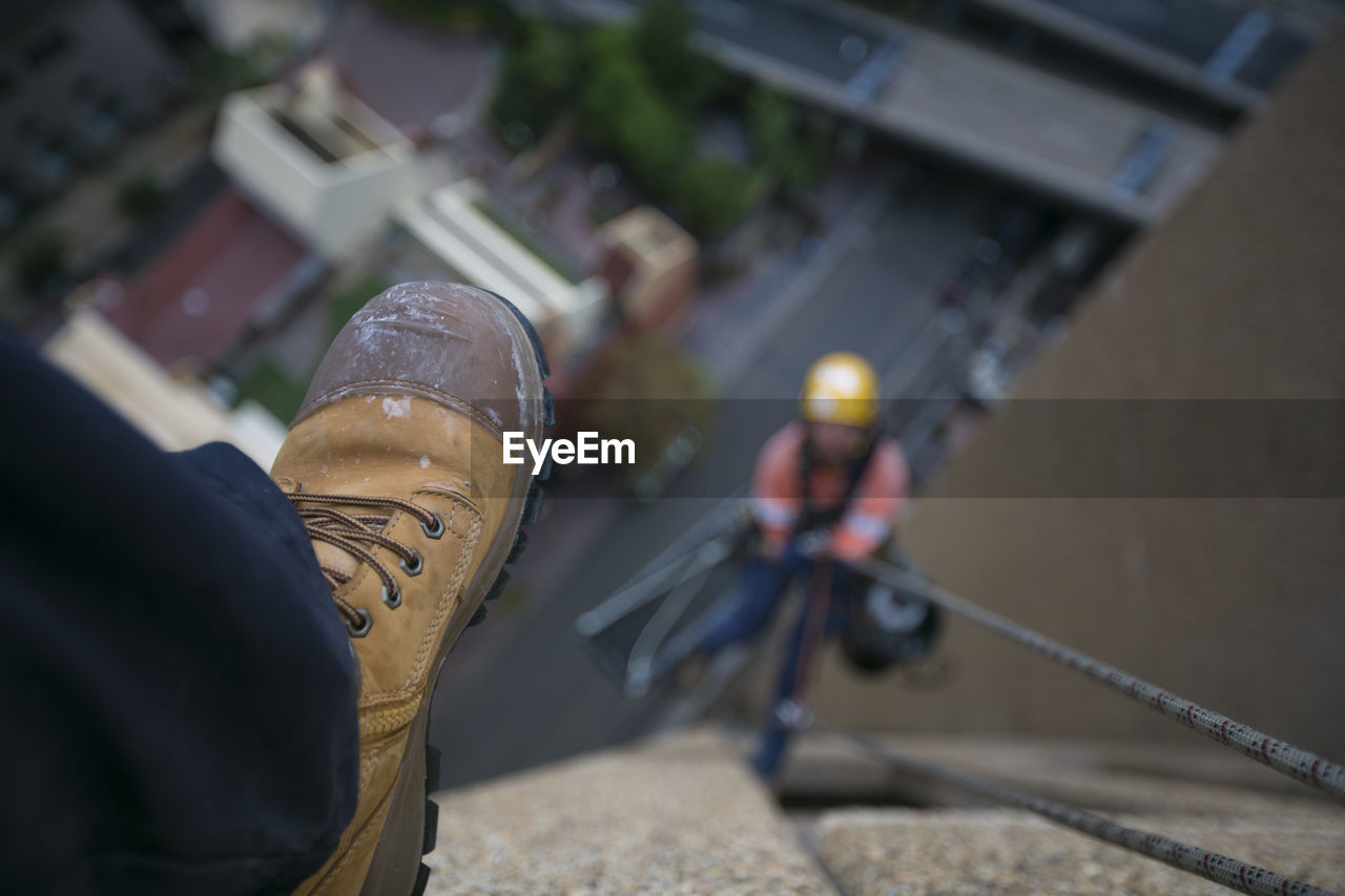 real people, one person, architecture, men, built structure, human leg, human body part, selective focus, building exterior, low section, shoe, focus on foreground, body part, lifestyles, working, occupation, outdoors, city, jeans