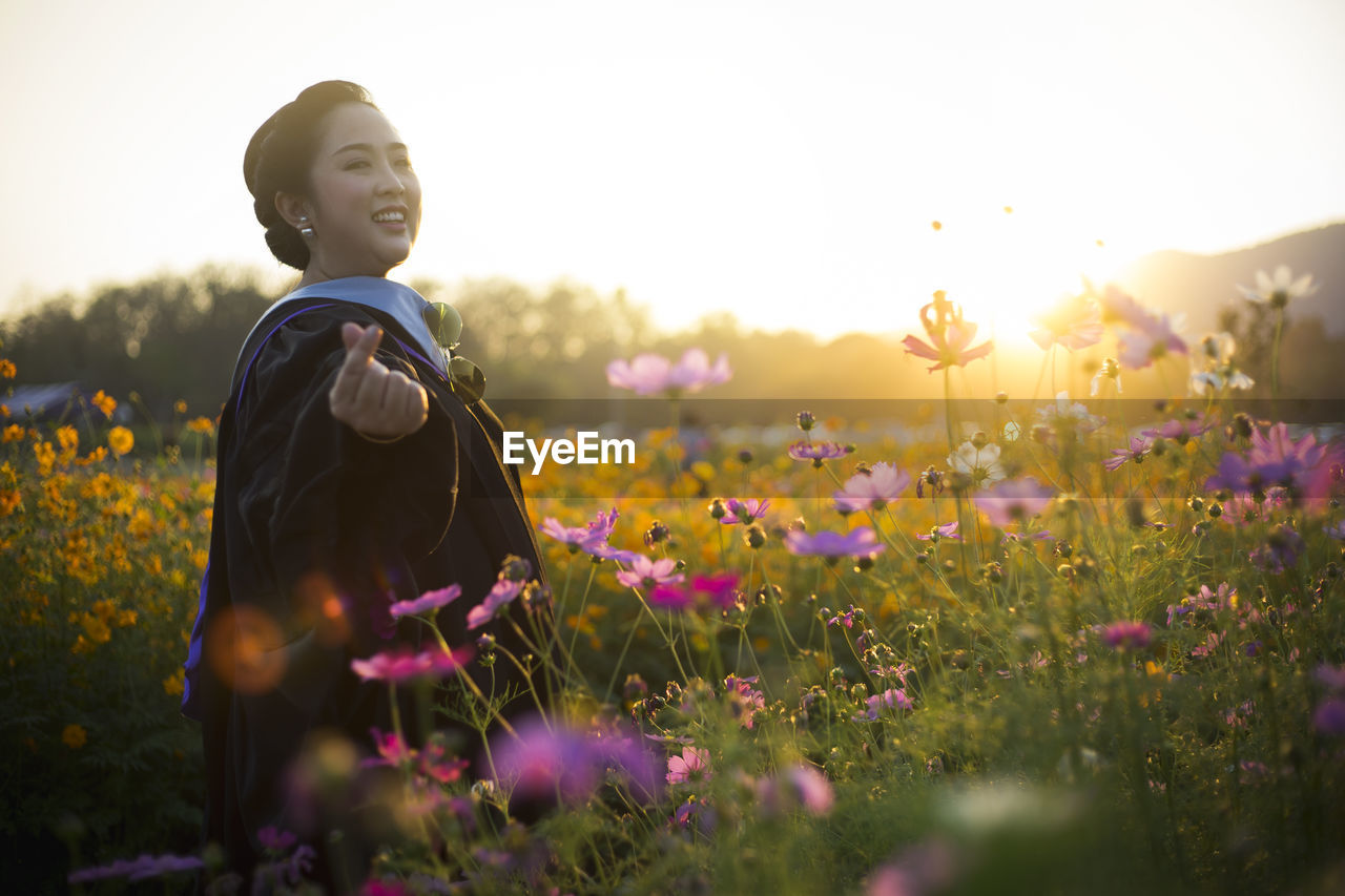 Side View Portrait Of Woman Smiling While Standing Amidst Flowers During Sunset