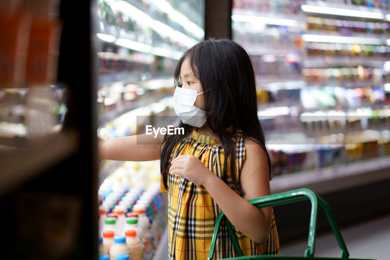Cute girl wearing mask shopping at supermarket
