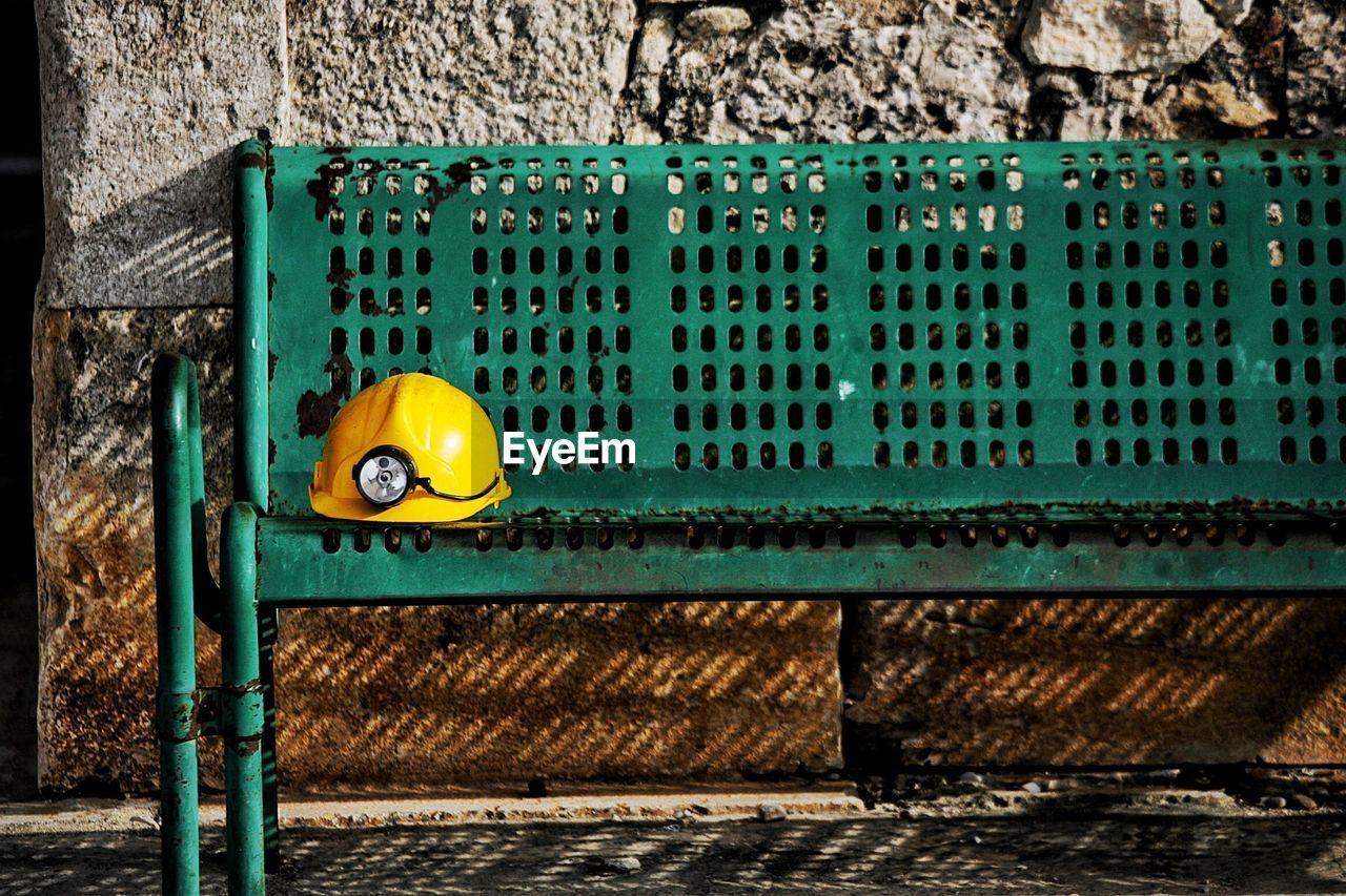 Yellow Hardhat With Headlamp On Bench During Sunny Day