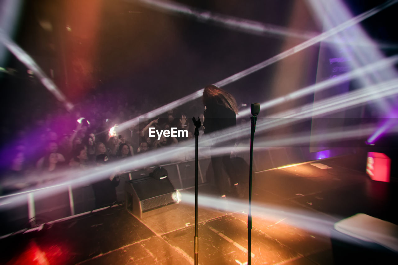 Rear View Of Female Musician Performing On Stage During Popular Concert