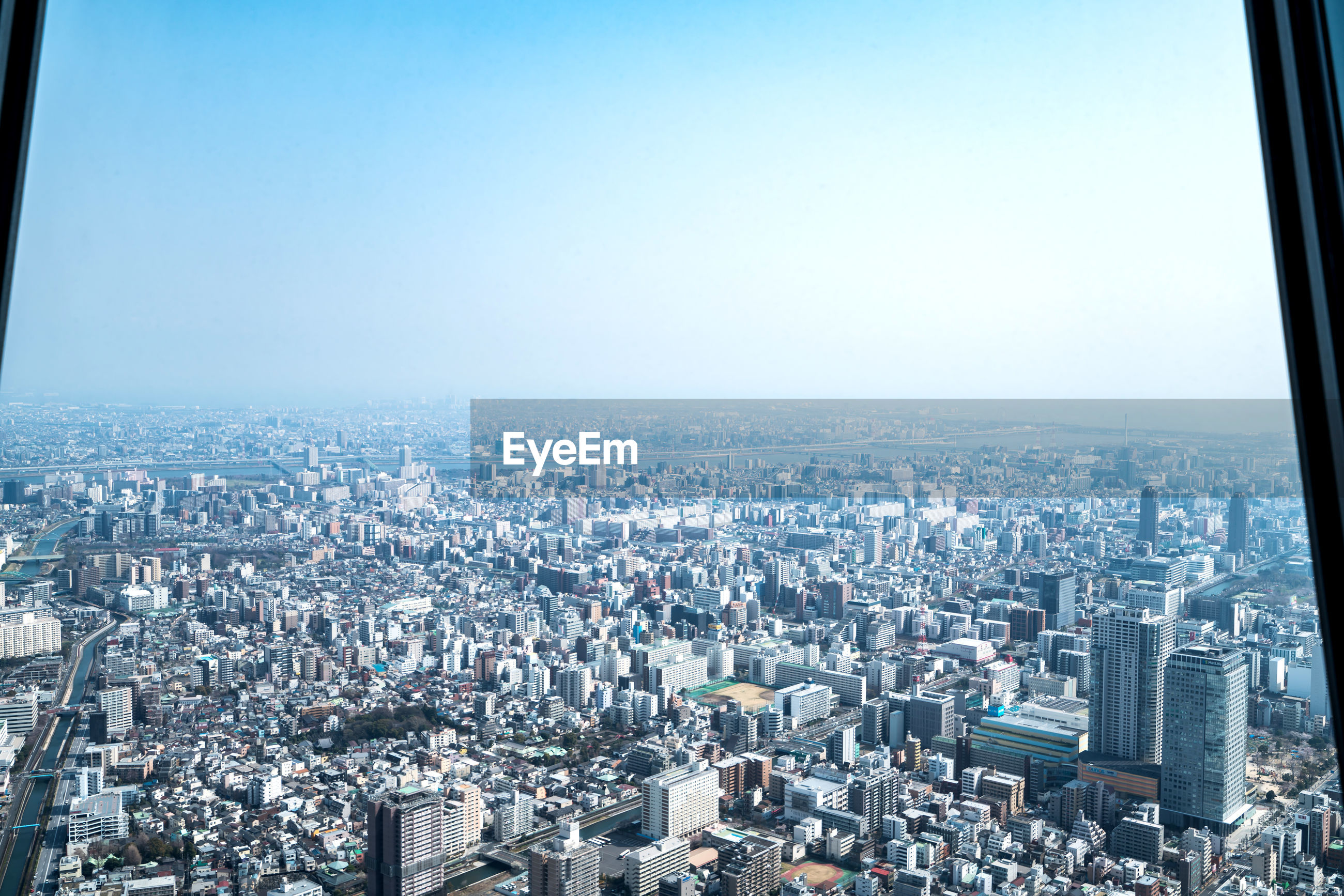 HIGH ANGLE VIEW OF CITY BUILDINGS AGAINST CLEAR SKY