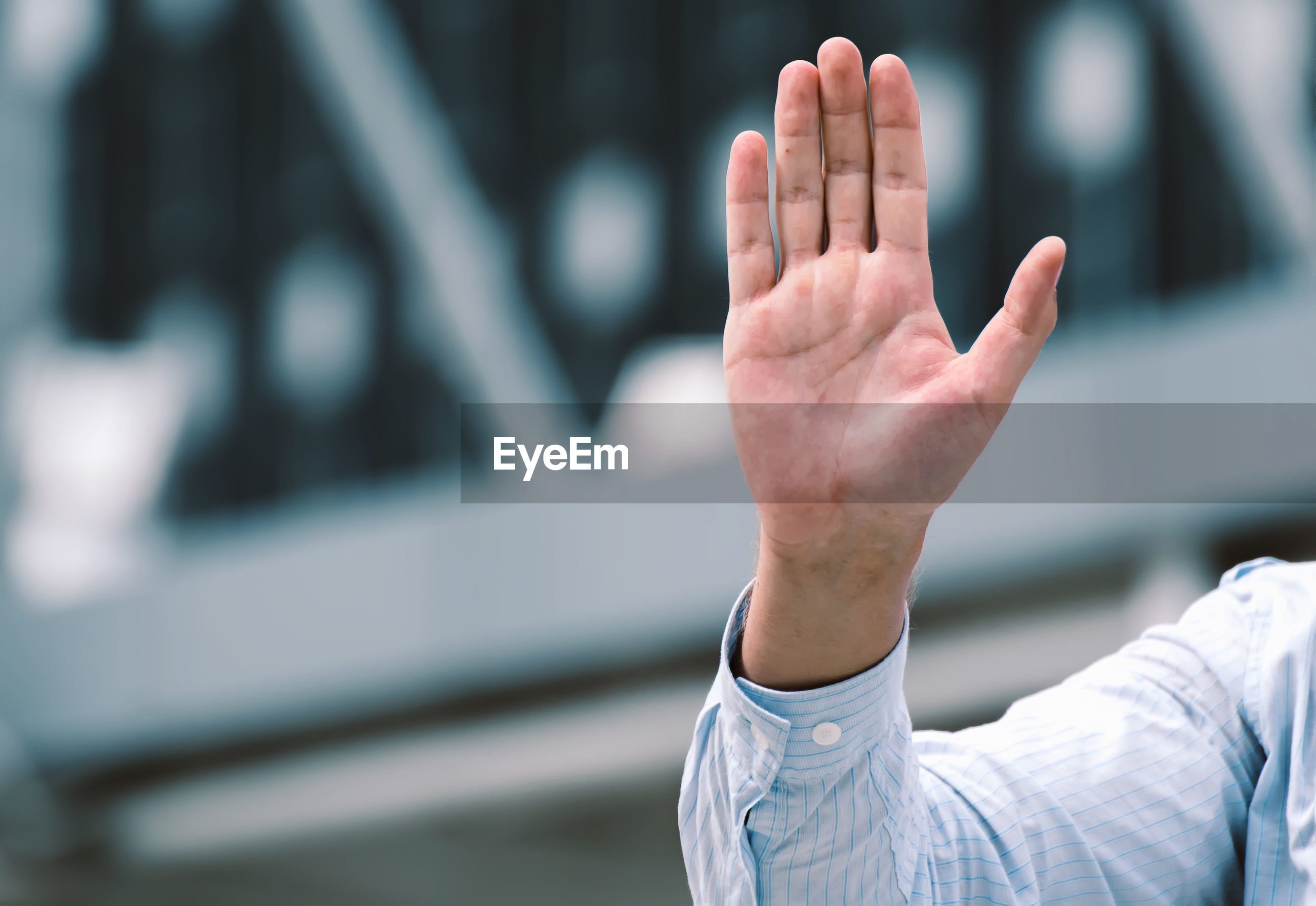 Cropped hand of man showing hand outdoors
