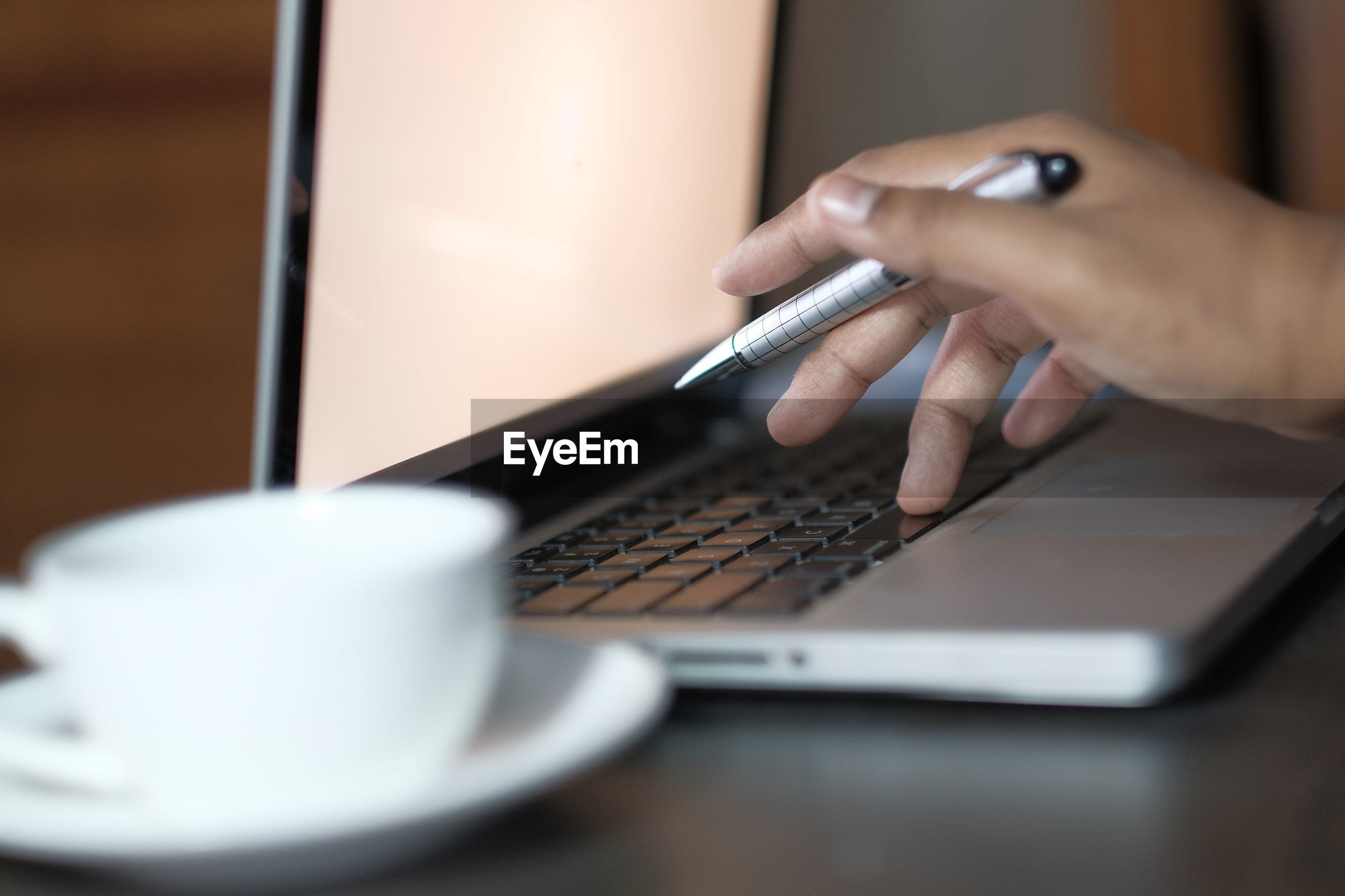 Close up of person using laptop on office desk