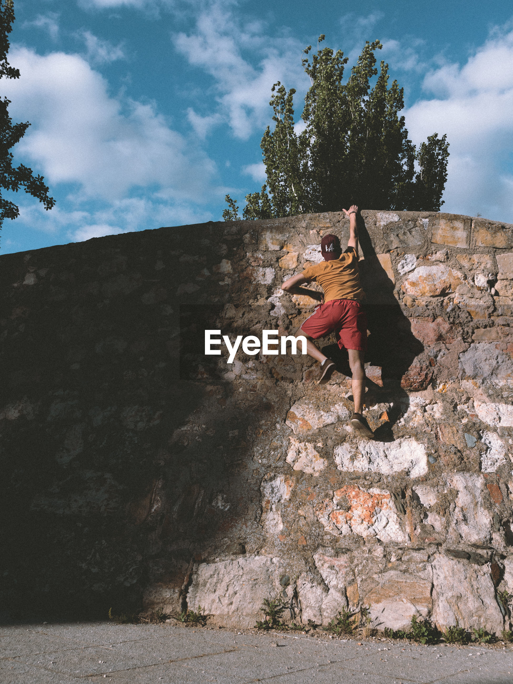 A man climbing a stone wall
