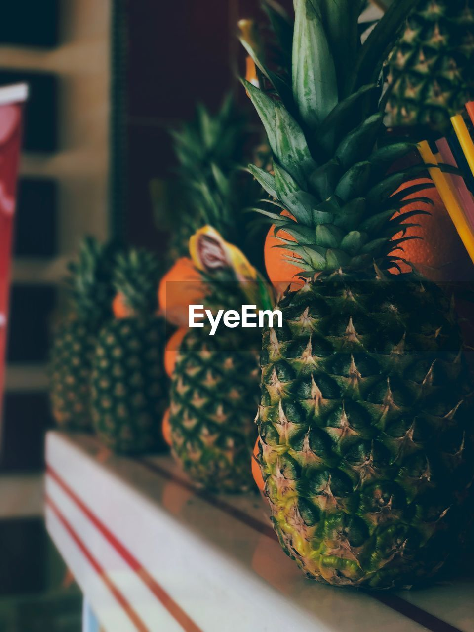 pineapple, green color, no people, potted plant, tropical fruit, succulent plant, indoors, close-up, fruit, cactus, healthy eating, plant, growth, wellbeing, food and drink, freshness, food, nature, still life, focus on foreground, houseplant