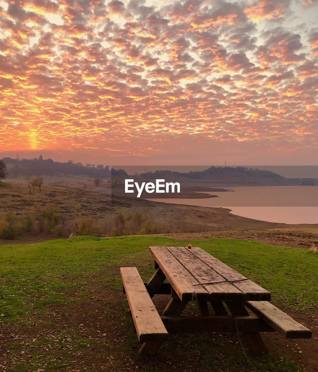 sunset, sky, scenics - nature, beauty in nature, tranquility, tranquil scene, nature, environment, grass, orange color, landscape, cloud - sky, idyllic, seat, bench, land, no people, field, non-urban scene, wood - material, outdoors, park bench
