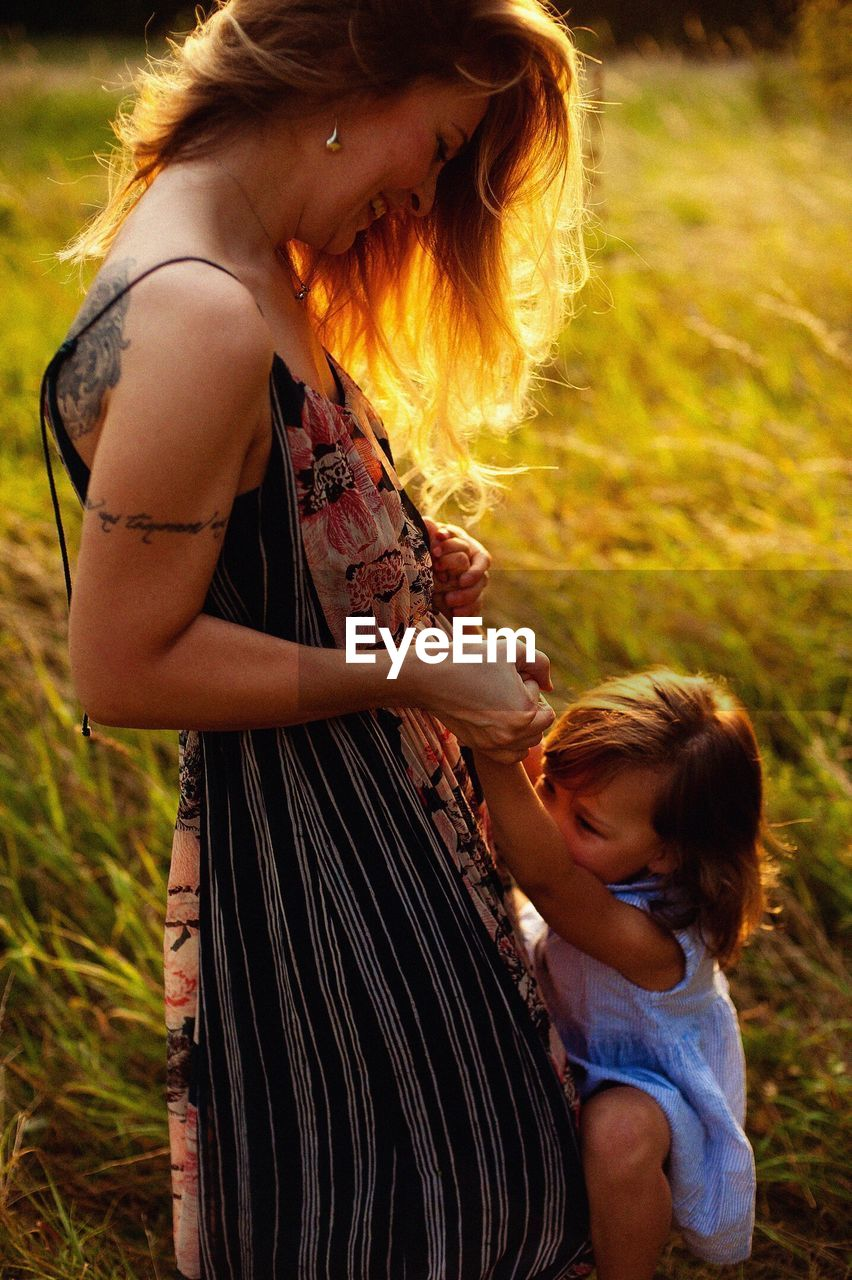 women, child, real people, field, land, childhood, family, females, girls, togetherness, two people, leisure activity, nature, casual clothing, mother, people, focus on foreground, three quarter length, lifestyles, hair, hairstyle, daughter, positive emotion, outdoors