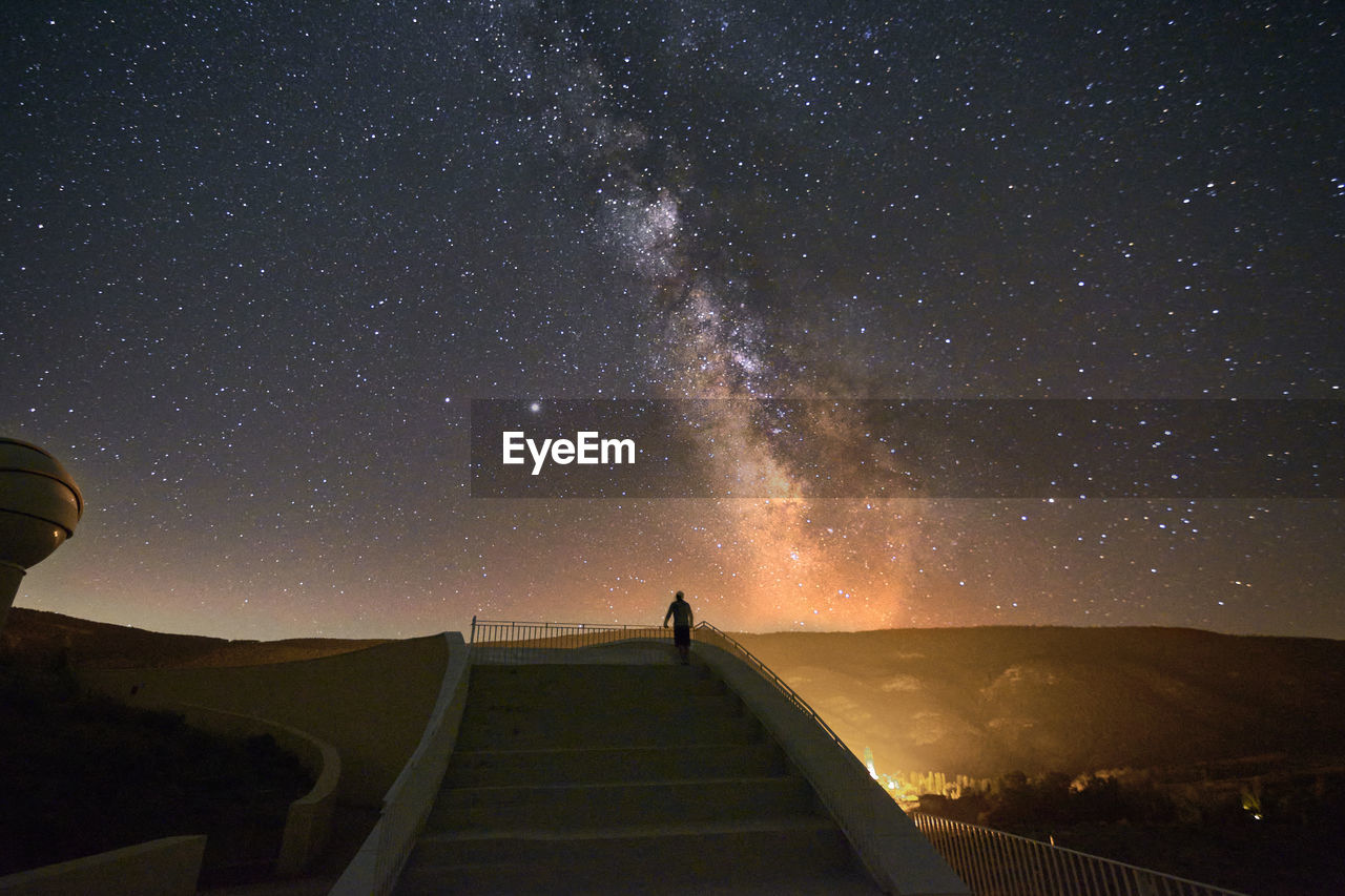 Person on grand staircase watching the milky way, stars, night time, long exposure