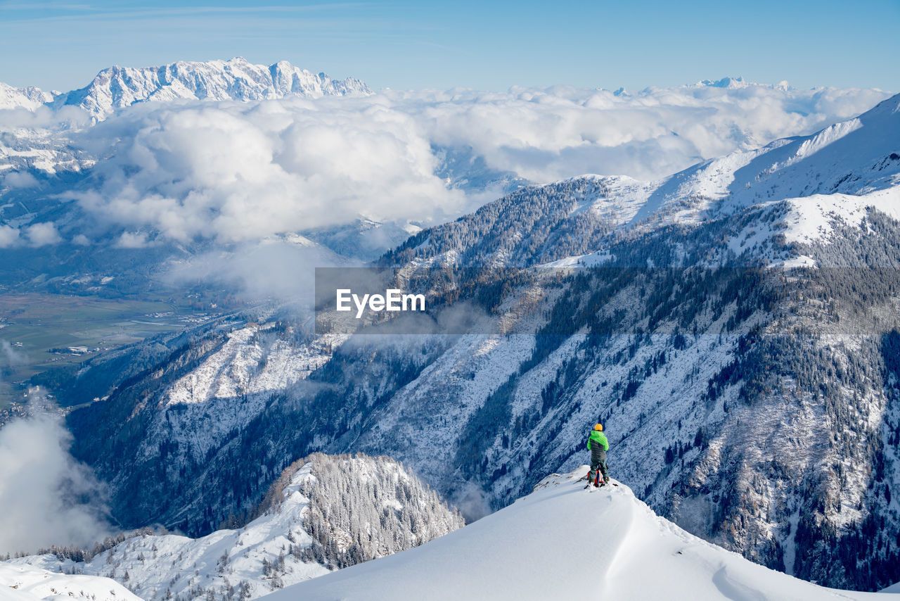 Hiker standing on snowcapped mountain peak while looking at landscape against sky