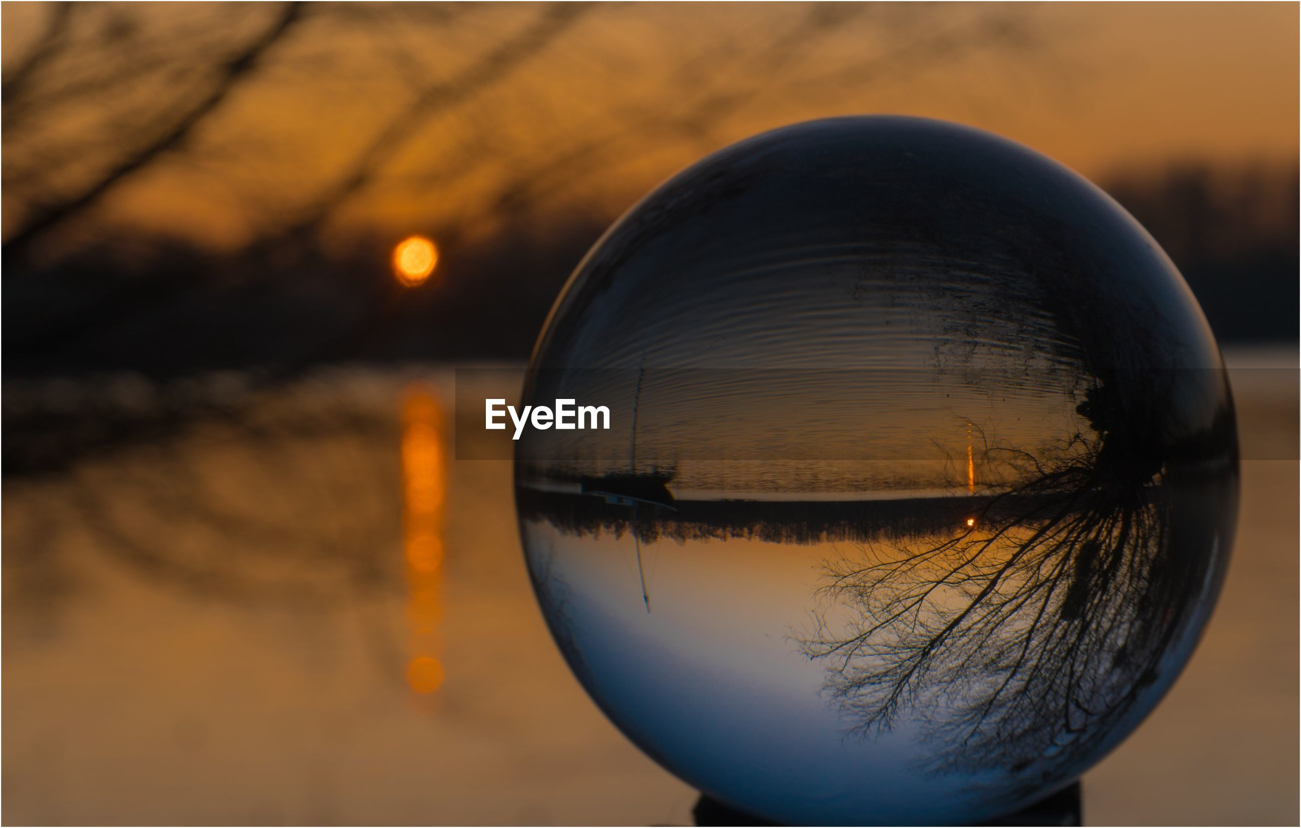Reflection of lake in crystal ball against sky