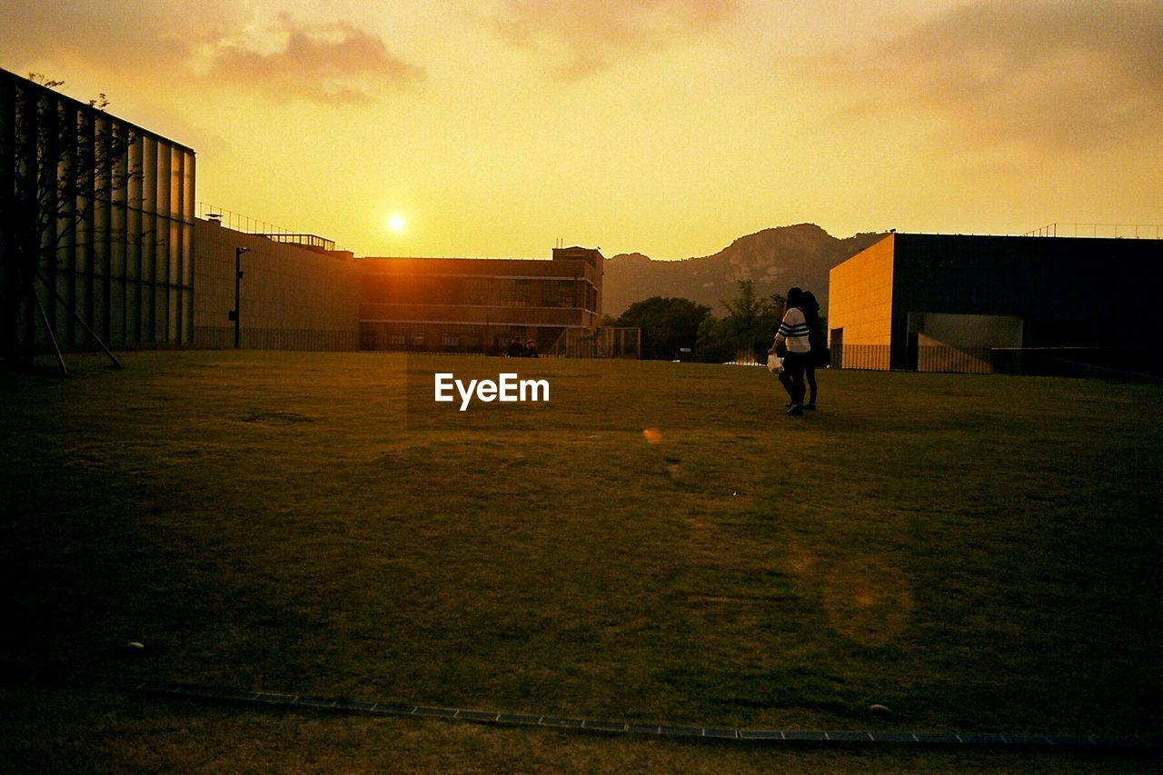 Friends Walking On Grassy Field By Buildings Against Sky During Sunset