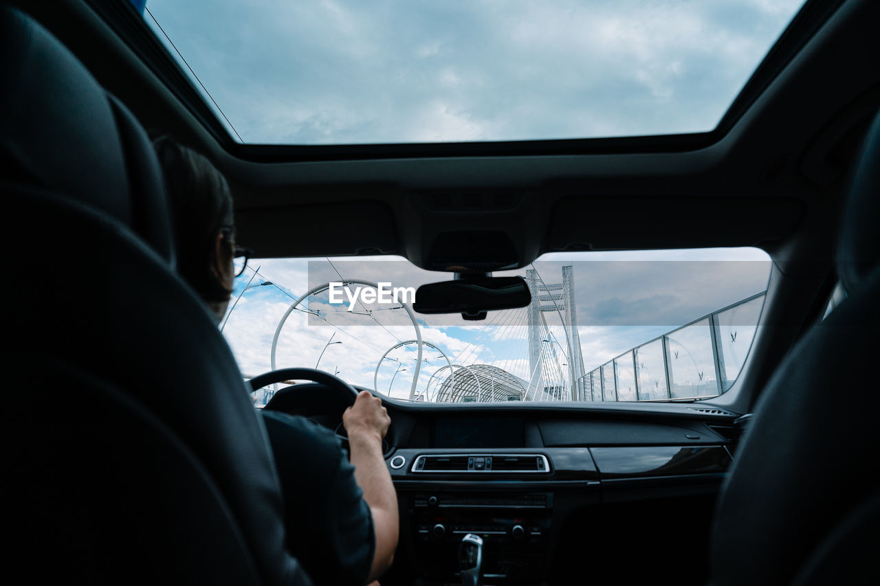 man driving car on cable bridge in the city