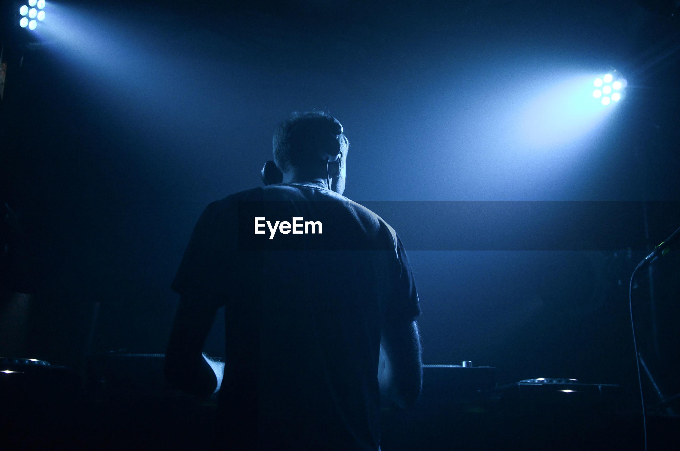 Rear view of dj performing at night