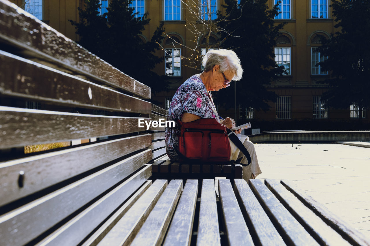Senior woman writing in paper while sitting on bench