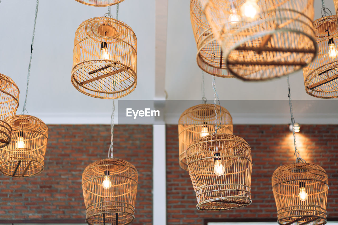 Low Angle View Of Illuminated Light Bulb In Birdcage Hanging On Ceiling