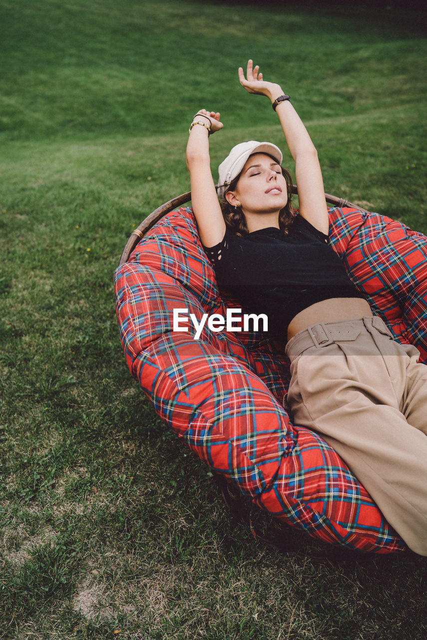 Young woman relaxing on chair over grass
