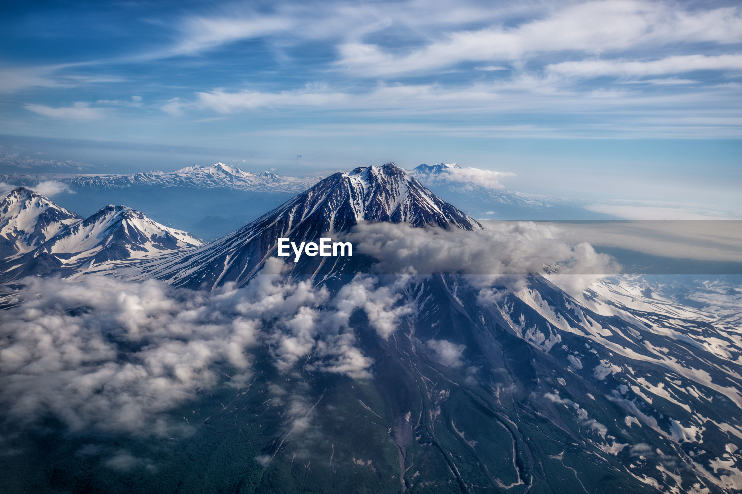 AERIAL VIEW OF SNOWCAPPED MOUNTAIN RANGE AGAINST SKY