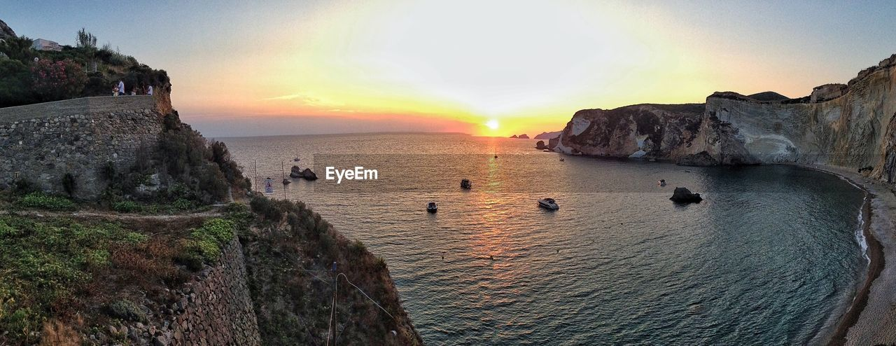 sunset, sea, rock - object, scenics, water, beauty in nature, nature, rock formation, sky, tranquil scene, tranquility, cliff, sun, horizon over water, real people, outdoors, leisure activity, travel destinations, lifestyles, beach, vacations, women, men, large group of people, day, people