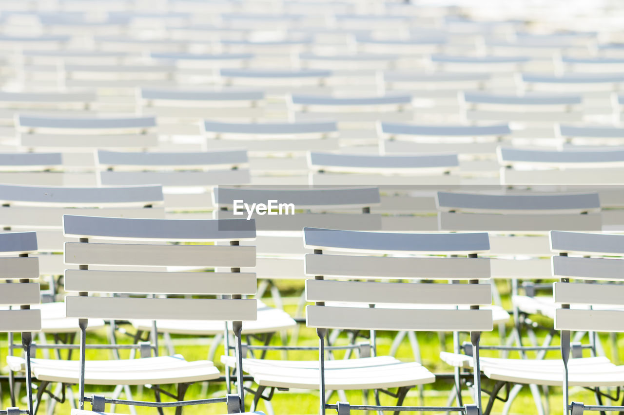 seat, chair, in a row, absence, empty, repetition, no people, white color, focus on foreground, side by side, large group of objects, table, order, arrangement, day, backgrounds, abundance, indoors, bleachers, full frame